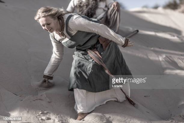 an individual female viking warrior in action on a sandy battlefield dune - historical reenactment stock photos and pictures