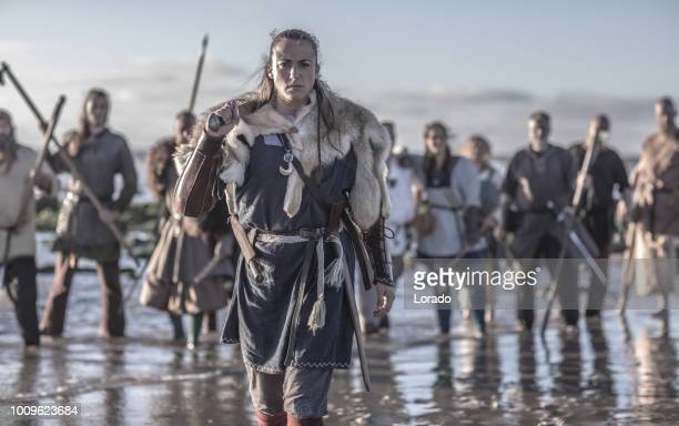 an individual female viking warrior in action on a watery battlefield - historical reenactment stock photos and pictures