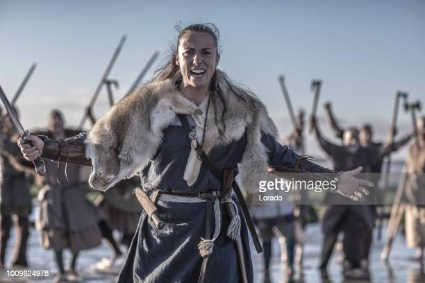 an individual female viking warrior in action on a watery battlefield - warrior person stock pictures, royalty-free photos & images