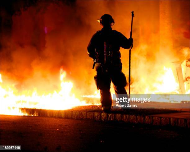 CONTENT] An individual fireman stands watch over a small brush fire approaching some homes in a suburban neighborhood in New Jersey