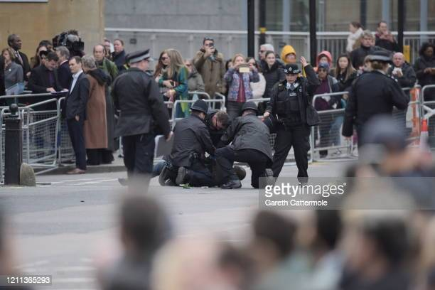 An individual is detained by police outside of the Commonwealth Day Service 2020 at Westminster Abbey on March 09 2020 in London England The...