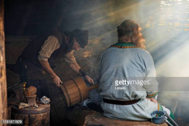 an individual viking blacksmith in a viking settlement - medieval stock pictures, royalty-free photos & images