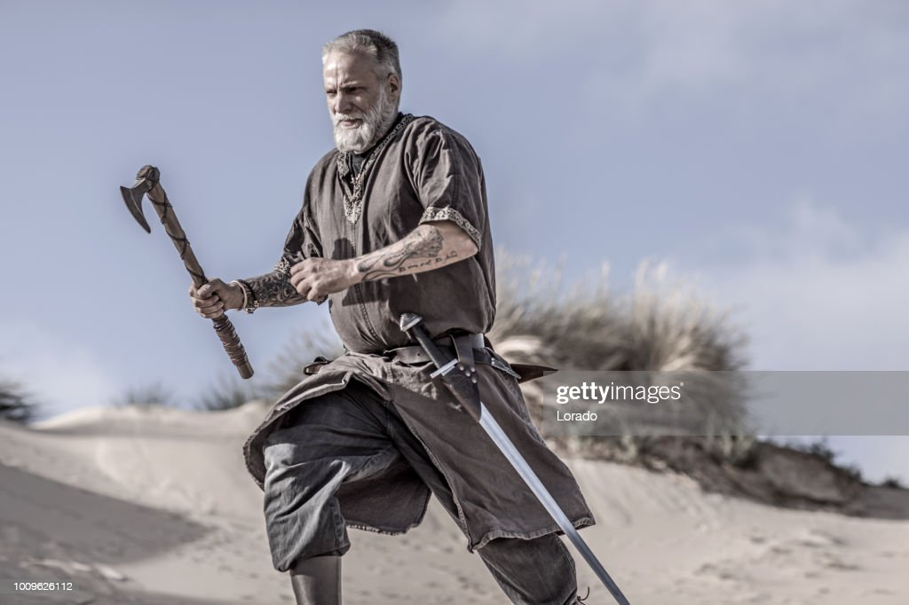 An individual viking warrior in action on a sandy battlefield dune : Stock Photo