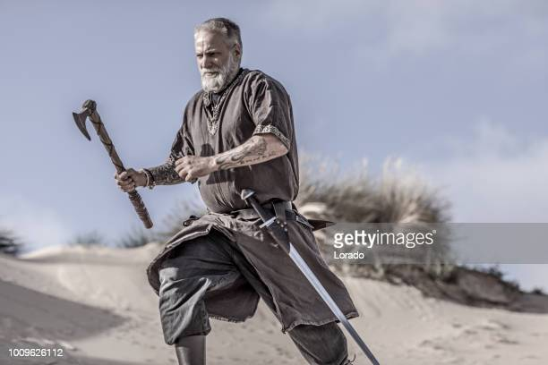 an individual viking warrior in action on a sandy battlefield dune - reenactment stock photos and pictures