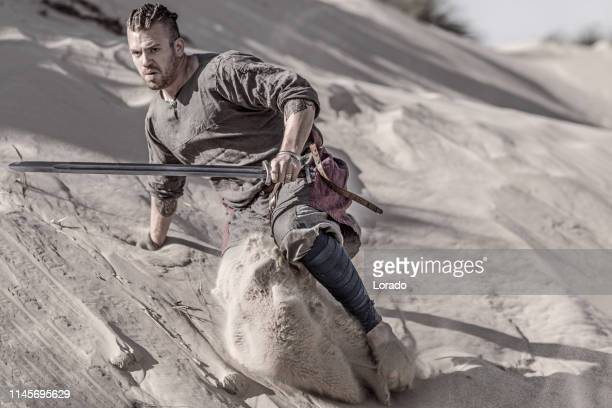 an individual viking warrior in action on a sandy battlefield dune - battlefield stock pictures, royalty-free photos & images