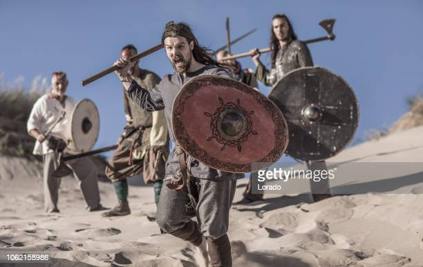 an individual viking warrior on a beach at the water's edge - barbarian stock photos and pictures