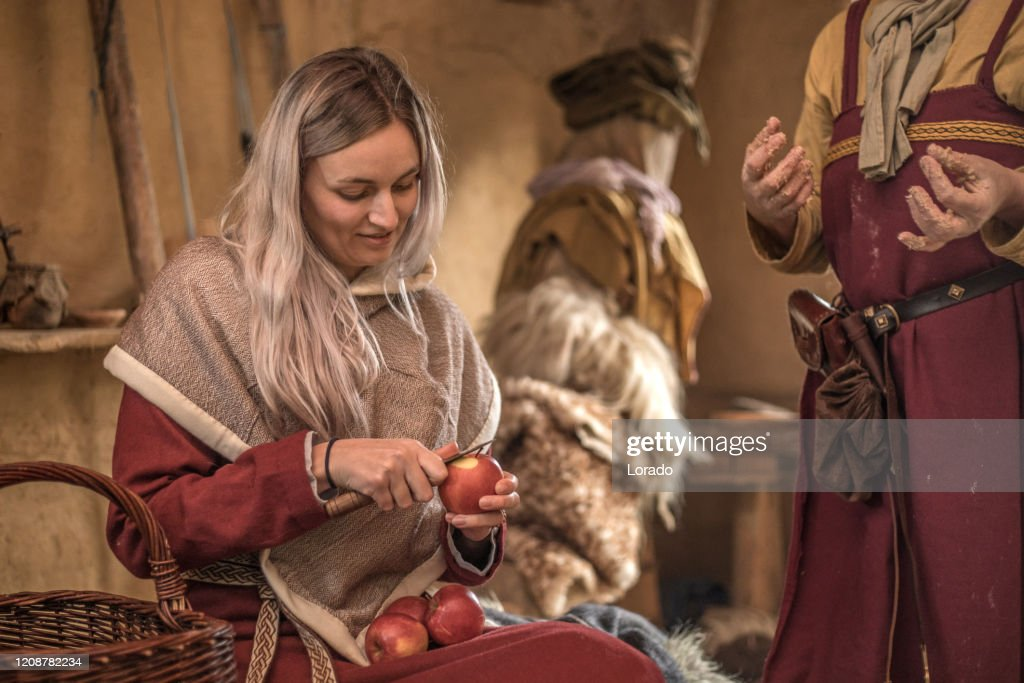 An individual viking woman doing daily chores in a viking village settlement : Stock Photo