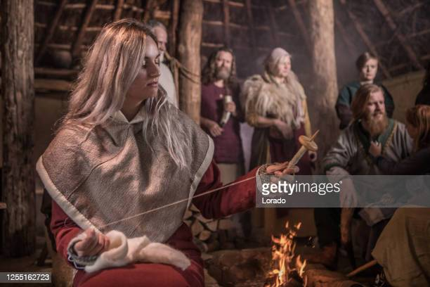 an individual viking woman doing daily chores in a viking village settlement - historical clothing stock pictures, royalty-free photos & images
