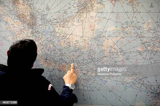 An Indonesia Search and Rescue officer inspects the operational air navigation map during the investigation of missing AirAsia QZ8501 at the crisis...