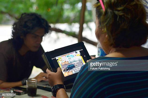 An Indonesia woman plays 'Tumpas Teroris' a game launched by the Indonesian police made for moral education to combat terrorism on a mobile devise at...