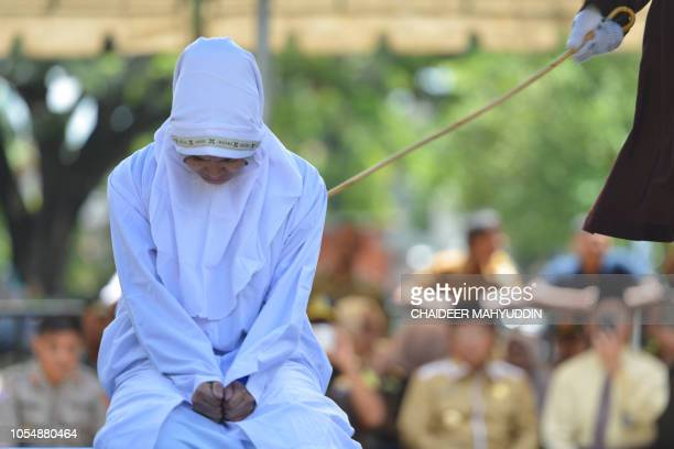 An Indonesian 21year old Muslim woman is cane in public after being caught in close proximity with her boyfriend in Banda Aceh on October 29 2018...