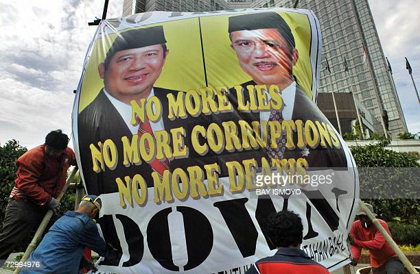 An Indonesian activist and workers tighten an anti-government campaign poster featuring Indonesian President Susilo Bambang Yudhoyono at one of the...
