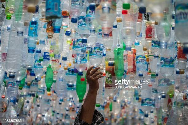 An Indonesian activist from ECOTON prepares an installation made with used plastic, including 4,444 bottles, collected from the river in Gresik on...