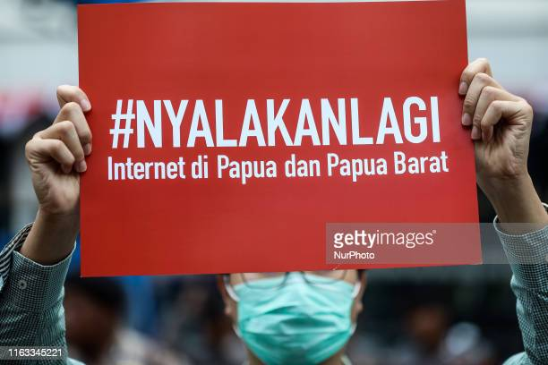 An Indonesian activist holds a poster calling for government unblocks the internet in West Papua during a demonstration protesting the Ministry of...