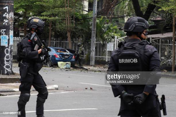 An Indonesian anti-bomb unit collects evidences as anti/terror police from Brigade Mobile stand by after a bomb exploded in Makassar on March 28,...