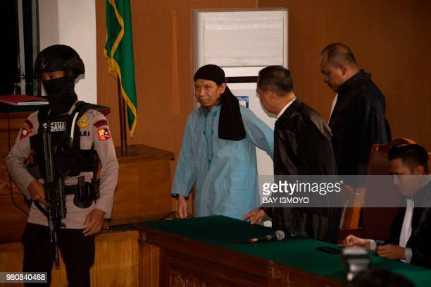 An Indonesian antiterror police officer escorts Aman Abdurrahman who is suspected of masterminding a 2016 gun and suicide attack in the capital...