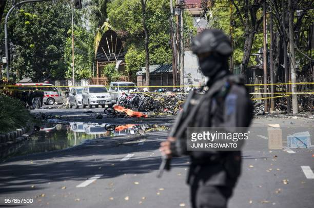An Indonesian antiterror policeman stands guard at the blast site following a suicide bomb outside a church in Surabaya on May 13 2018 A wave of...