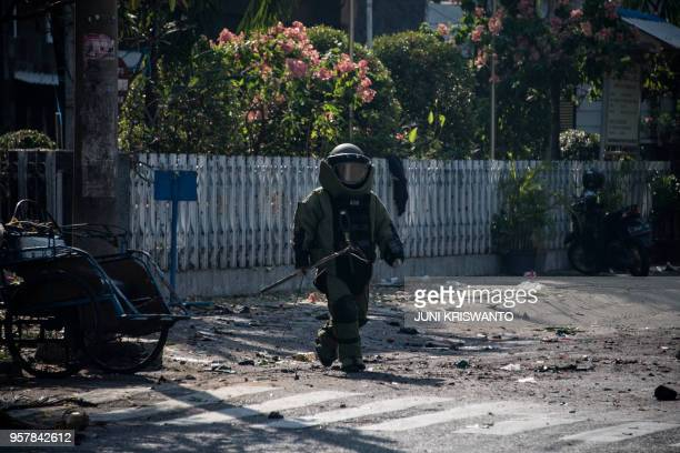 An Indonesian bomb squad member examines the site following a suicide bomb outside a church in Surabaya on May 13 2018 At least two people were...