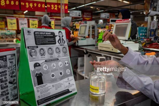 An Indonesian boy cleans his hands using alcohol gel at a store as Indonesia reports two cases of COVID19 on March 3 2020 in Yogyakarta Indonesia Two...