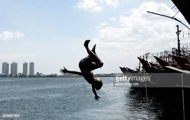 TOPSHOT An Indonesian boy jumps into the sea from a pier at the main fishing port of Muara Angke to cool off in Jakarta on February 5 2017 / AFP...