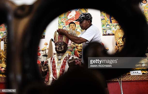 An Indonesian Buddhist cleans deity statues at a temple in Malang East Java province on January 21 2017 ahead of the Lunar New Year The Lunar New...