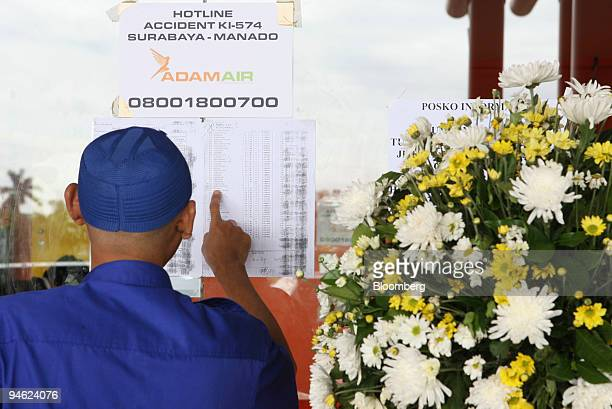 An Indonesian checks the passenger list of an Adam Air plane that went missing three days ago at the SoekarnoHatta International Airport in...