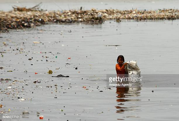 An Indonesian child collects garbages on the coast near a fishing village in Jakarta Indonesia on February 11 2016 According to scientists 8 million...