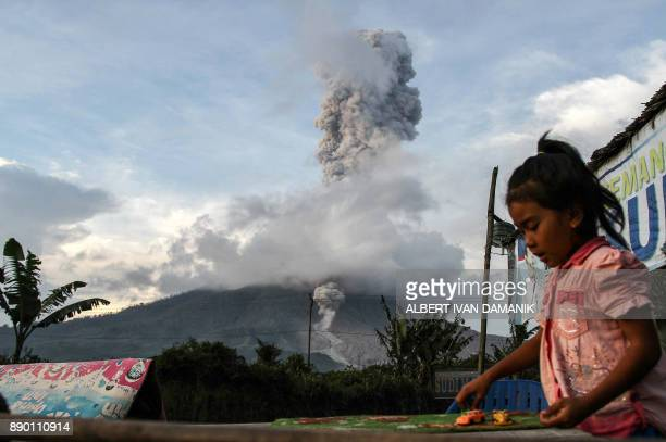 TOPSHOT An Indonesian child plays as volcano Mount Sinabung spews hot volcanic ash in Karo on December 11 2017 Mount Sinabung roared back to life in...