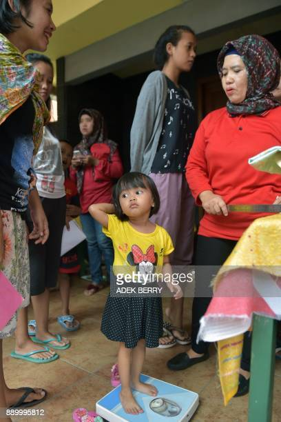 An Indonesian child stands on a weighing scale before being vaccinated against diphtheria at a village clinic in Jakarta on December 11 2017 Millions...