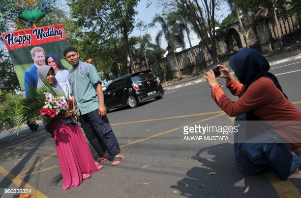 An Indonesian couple pose for a picture in front of a poster of Britain's Prince Harry and his wife Meghan Markle in Solo Central Java on May 20 2018...