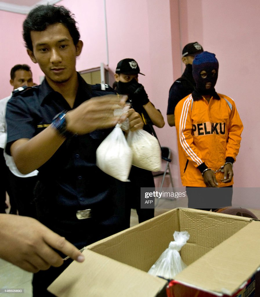 An Indonesian customs official inspect packs of heroin and crystal methamphetamine seized from an Indonesian susupect, seen at right covered with hood, after he was arrested at Banda Aceh airport in Aceh province on June 18, 2012 . The suspect was caught carrying two kilograms of heroin and one kilogram of crystal methamphetamine with a total worth of 10 billion Rupiah ( 1.06 million USD) after arriving from Malaysia.