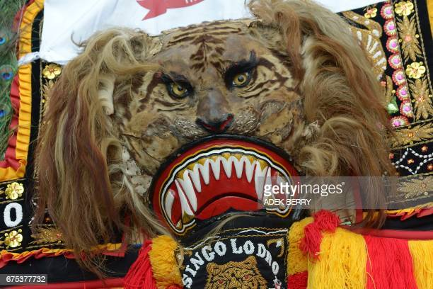 An Indonesian dancer in lion costume performs the 'Reog Ponorogo' dance during a May Day protest in Jakarta on May 1 2017 Millions of May Day...