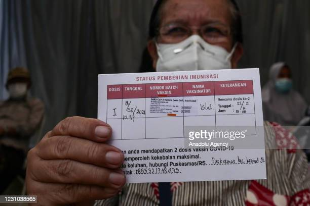 An Indonesian elderly health worker shows a vaccine certificate after receive first dose of SinoVac COVID-19 vaccine at Kramat Jati district health...