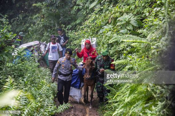 An Indonesian election worker on horseback assisted by police and army officials transports ballot boxes and election material to a remote village in...
