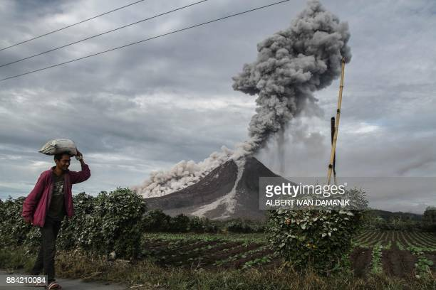TOPSHOT An Indonesian farmer passes a field as Mount Sinabung volcano spews thick smoke into the air in Karo North Sumatra on December 2 2017 Mount...