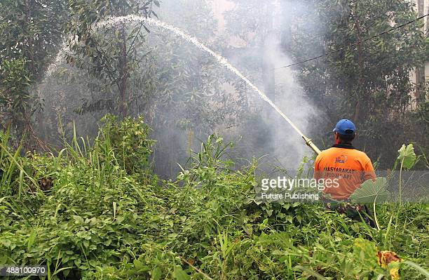 An Indonesian fireman tries to extinguish forest fire on September 13 2015 in Riau Indonesia The thick haze has forced the repeated cancellation of...