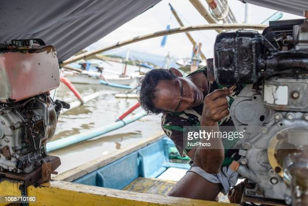 An Indonesian fisherman prepares his boat at the old fishers port near Perancak village Bali Indonesia in December 2018