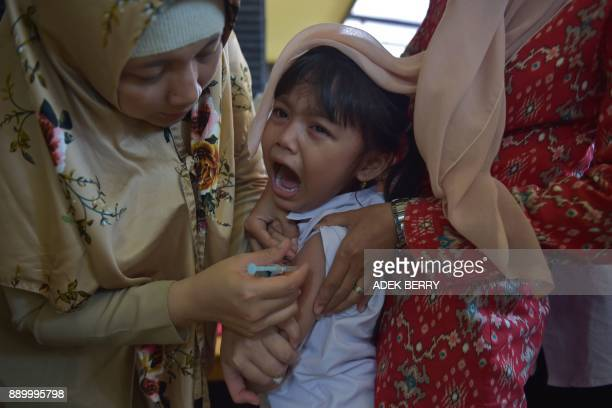 An Indonesian girl cries as she receives a vaccination shot against diphtheria at a village clinic in Jakarta on December 11, 2017. Millions of...