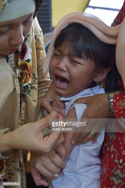 An Indonesian girl cries as she receives a vaccination shot against diphtheria at a village clinic in Jakarta on December 11 2017 Millions of...