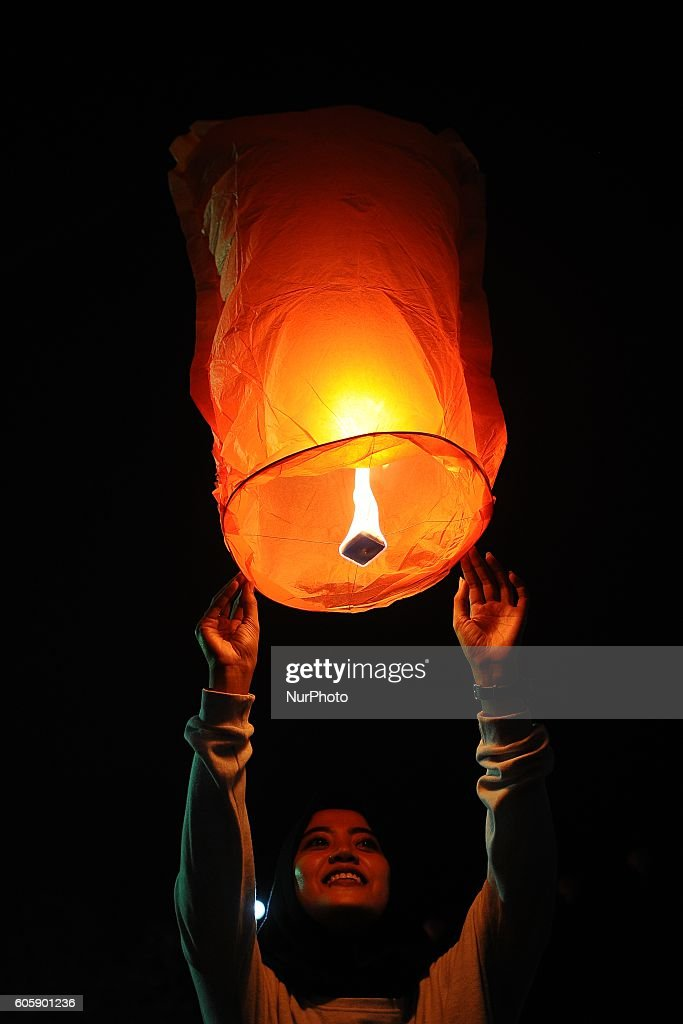 An Indonesian Girl Releases A Paper Lantern During Moon Cake Mid Autumn Festival