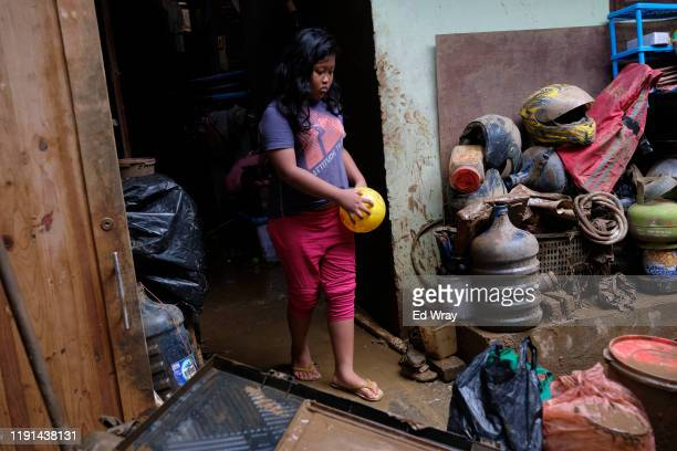 An Indonesian girl walks past household goods waiting to be cleaned after floodwaters tore through her neighborhood on January 3, 2020 in Jakarta,...