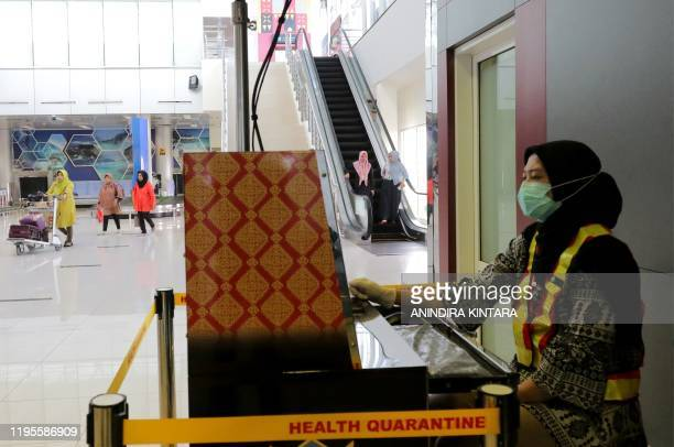 An Indonesian health officer screens passengers with a thermal scanner at the Depati Amir airport in Pangkal Pinang on Bangka Belitung island on...