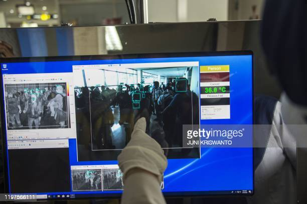 An Indonesian health official checks a screen of thermal scanner as passengers arrive at the Juanda International airport in Sidoarjo, East Java on...
