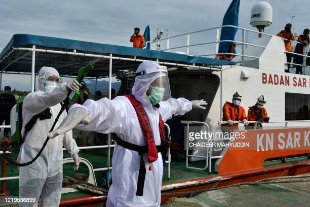 An Indonesian health quarantine official wearing a protective gear amid the COVID-19 coronavirus pandemic sprays disinfectant after in a medical...