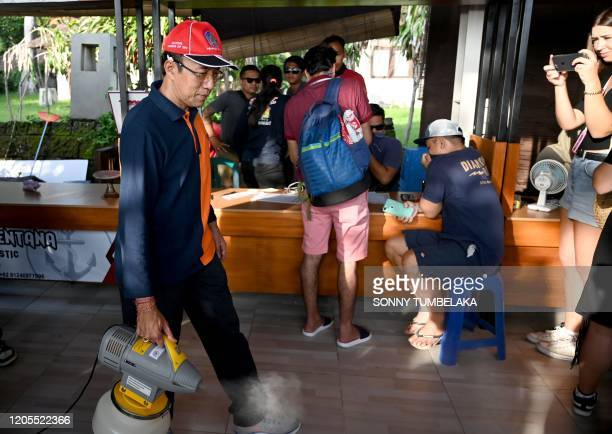 An Indonesian health worker sprays disinfectant at the embarkment to cross from Sanur to Nusa Penida island, on Indonesia resort island of Bali on...