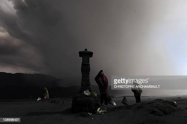 An Indonesian Hindu devotee offers prayers as he stands in the caldera surrounding the ashshooting Mount Bromo volcano outside the village of Cemoro...