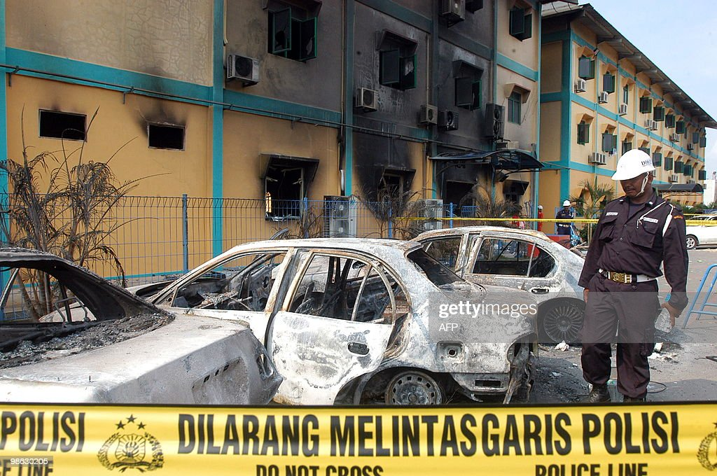 An Indonesian internal security officer examines damaged cars following a riot inside PT Drydock World Graha factory buildings in Batam city on April 23, 2010. Indonesian police said on April 23, they have named Indian company executive Ghesa Prabaharan as a suspect over an insulting remark that triggered a riot by thousands of factory workers. Prabaharan is alleged to have called Indonesian people 'stupid,' and could risk up to four years in jail, police said.