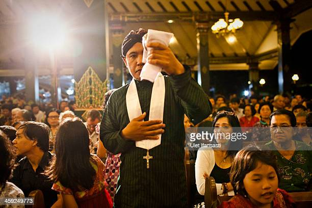 An Indonesian Javanese Christian wears traditional outfits as he attend Christmas eve mass at Ganjuran church on December 24 2013 in Yogyakarta...