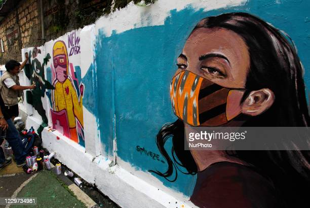 An Indonesian local artist draws a coronavirus awareness graffiti on a walls of the houses for the residents to educate and encourage public optimism...