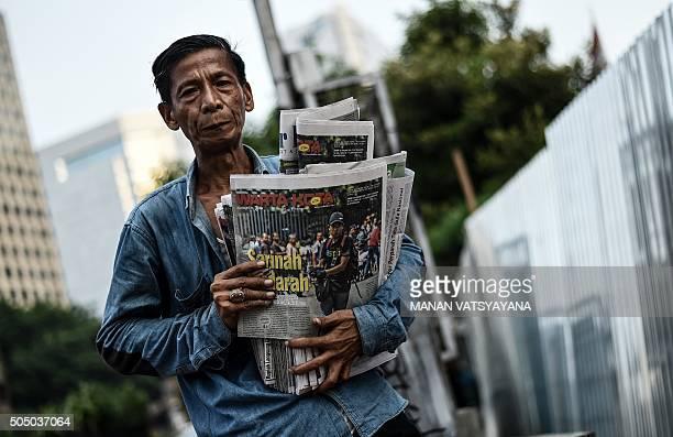 TOPSHOT An Indonesian man carries newspapers bearing pictures of an alleged gunman while he walks past the damaged Starbucks building in Jakarta on...